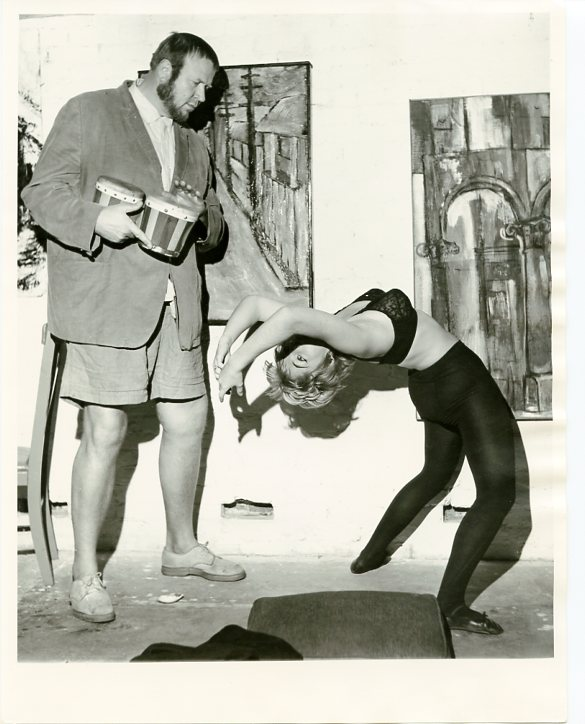 Original photograph of Eric Nord playing bongos while a beatnik woman in black tights and bra dances next to him with abstract paintings on the wall, ca. 1960. Eric NORD.