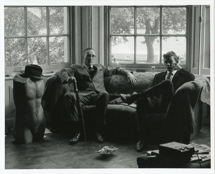An original photograph (recent print) of William Burroughs and an unidentified young man sitting on a couch in front of a huge bay window in an English mansion. William S. BURROUGHS.