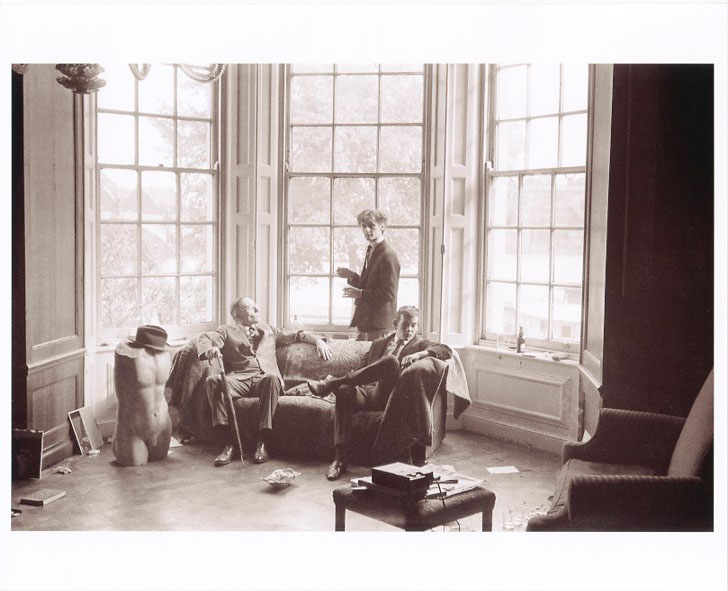 An original b&w photograph (recent print) of William Burroughs and another man sitting on a couch in front of a huge bay window in an old English mansion. William S. BURROUGHS.