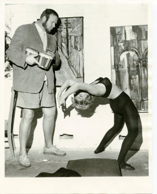 Original photograph of Eric Nord playing bongos while a beatnik woman in black tights and bra...