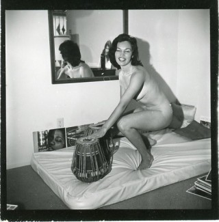 Print cut from a contact sheet showing a naked woman crouched on a mattress playing tabla drums....