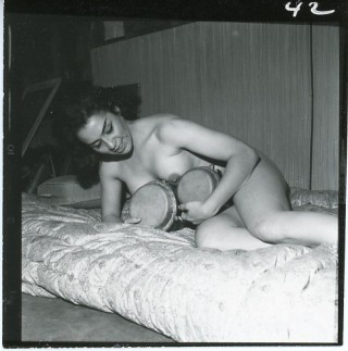 Print cut from a contact sheet showing a naked woman lying on a mattress holding bongo drums...