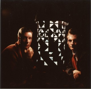 Color photograph (recent print) of Brion Gysin and Ian Sommerville sitting on either side of a dream machine, looking directly into the camera. Brion GYSIN, Herman LEONARD.